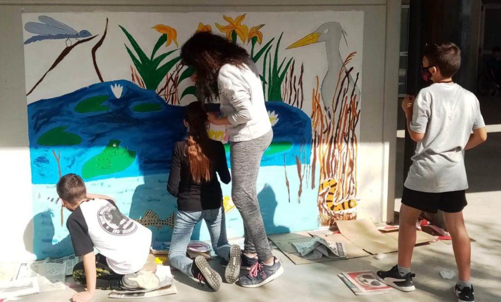 Quatre alumnes de 6t pintant un dels murals a la paret del gimàs de l'escola