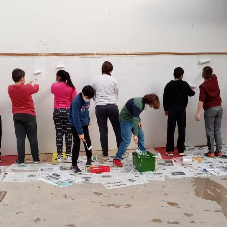 Alumnes de set emblanquina una de les parets del gimnàs amb rodets.
