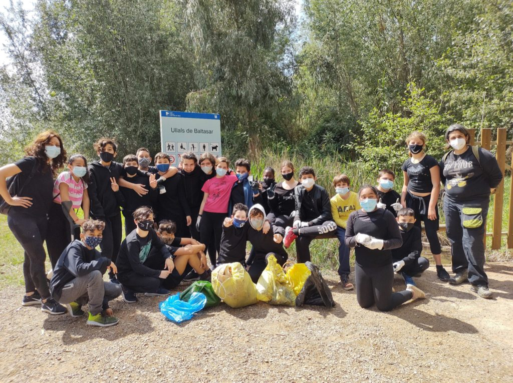 Grup d'alumnes als Ullals de Baltasar mostrant la brossa recollida durant la setmana de recollida selectiva d'escombraries en espais naturals.