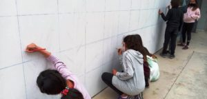 Alumnat quadriculant el mural a la paret del gimnàs