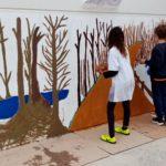 Alumnat de 6t està donant color al mural gran de l'escola.